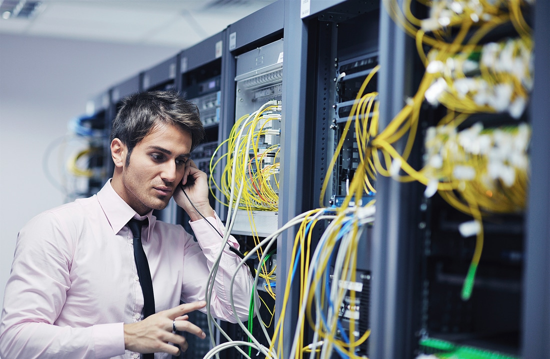 Male business professional in a server room calling IT support to fix a technical problem