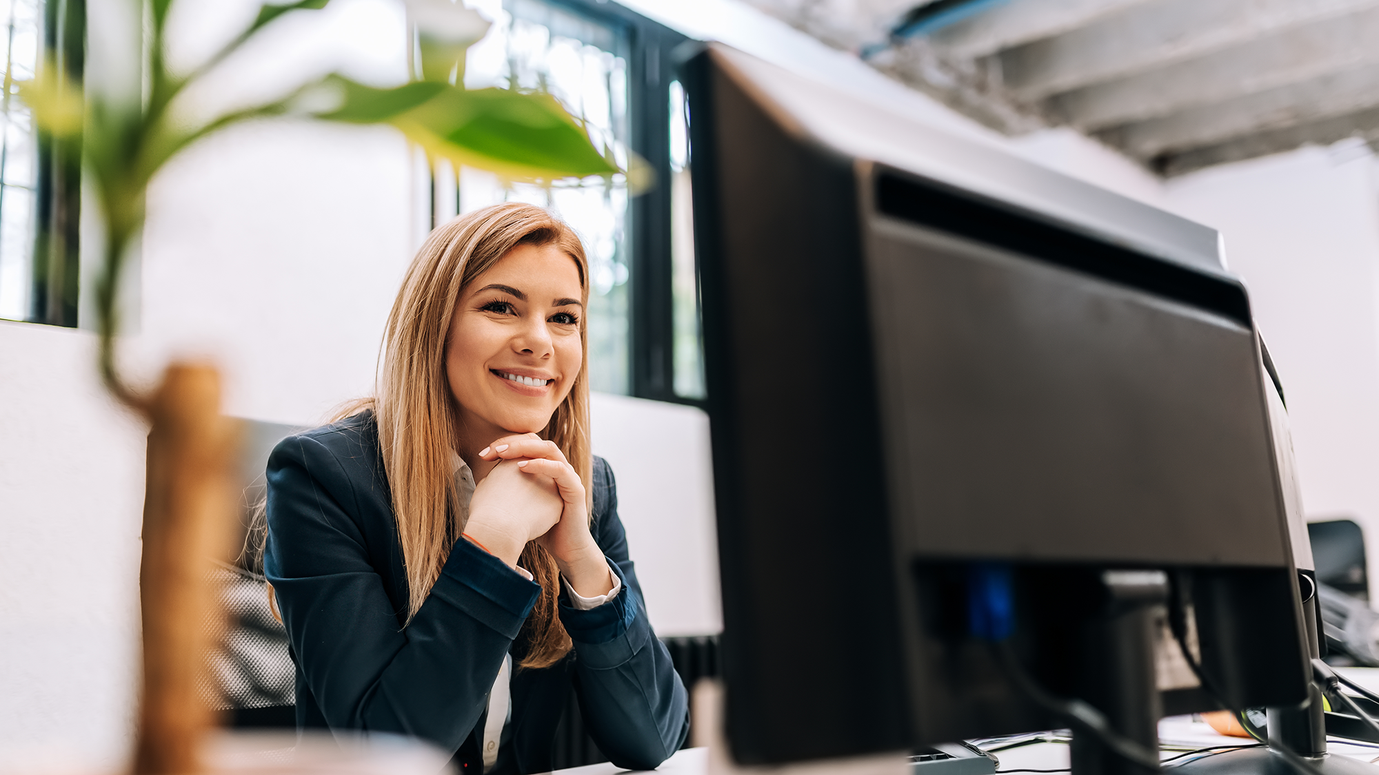 Smiling businesswoman in front of desktop computer