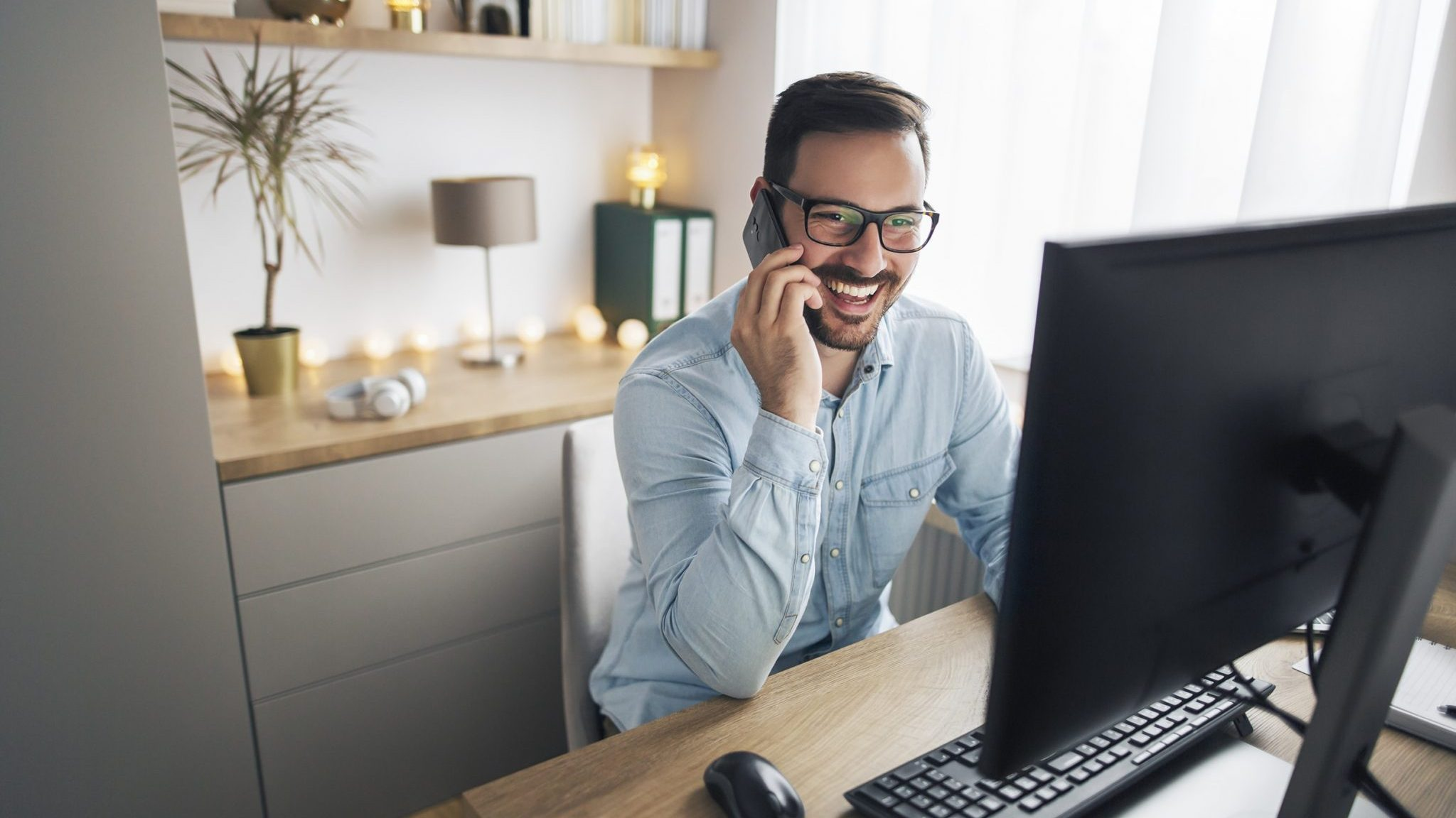 Happy manager on cell phone calling client from home office